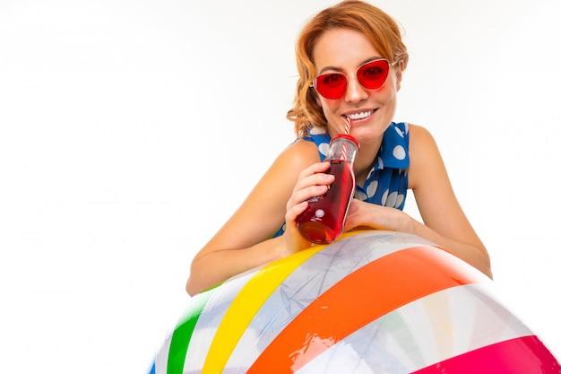 Alegre mulher com cabelo vermelho justo segura uma bola, imagens isoladas no fundo branco