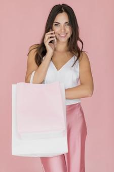 Alegre mulher com sacola de compras, falando no smartphone