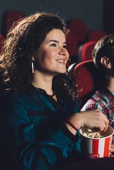 Alegre mulher comendo pipoca no cinema Foto gratuita