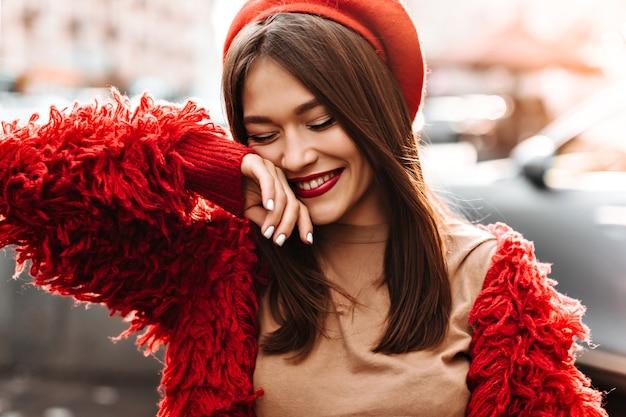 Alegre mulher de cabelos escuros com batom cor de vinho, vestida com uma elegante jaqueta de lã superdimensionada e chapéu vermelho ri, cobrindo o rosto com a mão.