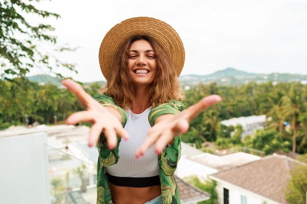 Alegre mulher de chapéu de palha, se divertindo, estende as mãos para a câmera.
