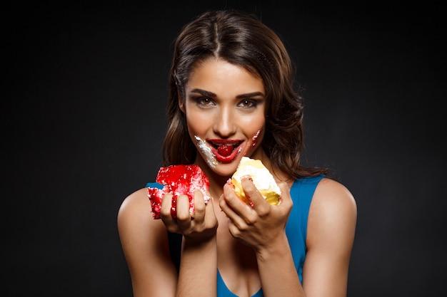 Alegre mulher de vestido azul, comer dois pedaços de bolo
