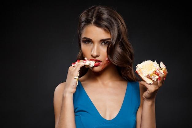 Alegre mulher de vestido azul, comer pedaço de bolo