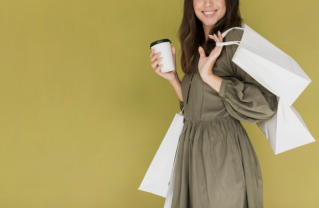 Alegre mulher de vestido com café e redes de compras