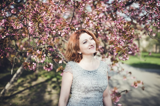Alegre mulher debaixo da árvore de sakura floresce.