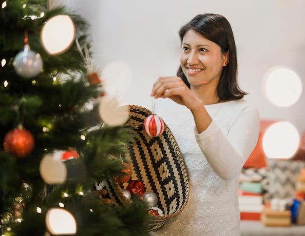 Alegre mulher decorando a árvore de natal