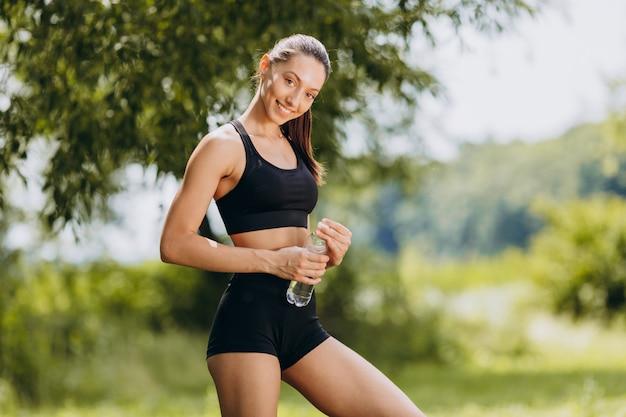 Alegre mulher desportiva em pé no parque, segurando uma garrafa com água ao ar livre.