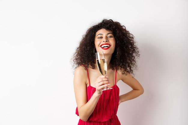 Alegre mulher elegante com cabelo escuro encaracolado, usando vestido de festa, comemorando aniversário no dia dos namorados, bebendo champanhe em uma taça e sorrindo para a câmera, fundo branco.