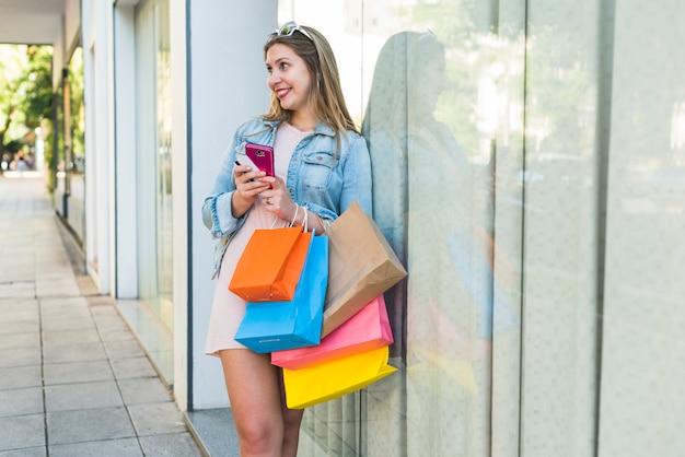 Alegre mulher em pé com sacolas de compras, smartphone e cartão de crédito
