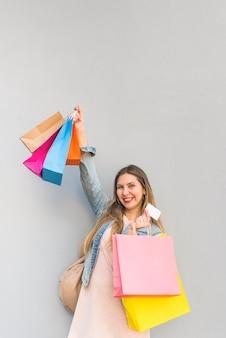 Alegre mulher em pé com sacos de compras e cartão de crédito na parede de luz
