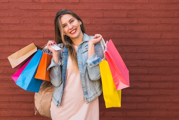 Alegre mulher em pé com sacos de compras e cartão de crédito na parede de tijolo vermelho