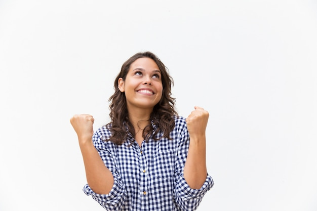 Alegre mulher feliz fazendo vencedor gesto e olhando para cima