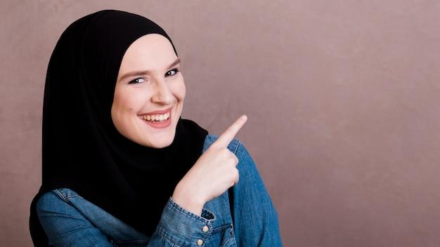 Alegre mulher islâmica apontando o dedo para algo