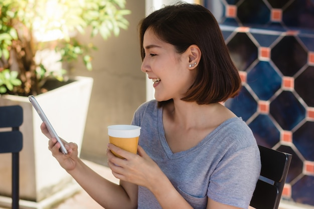 Alegre mulher jovem asiática sentado no café a beber café e usando smartphone para falar