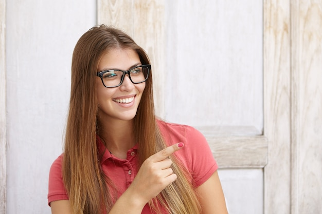 Alegre mulher jovem, com cabelos longos e lisos, apontando o dedo indicador para longe