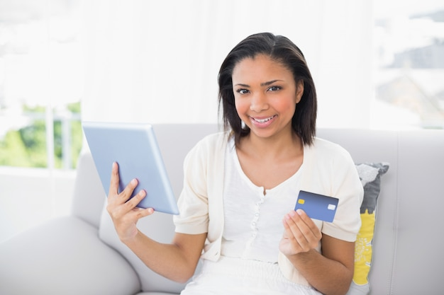 Alegre mulher jovem de cabelos escuros em roupas brancas, compras on-line com um tablet pc