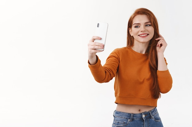 Alegre mulher jovem e atraente com cabelo ruivo tirando selfie antes de ir para a festa, fazer postar internet, segurar o smartphone olhando para o celular na frente