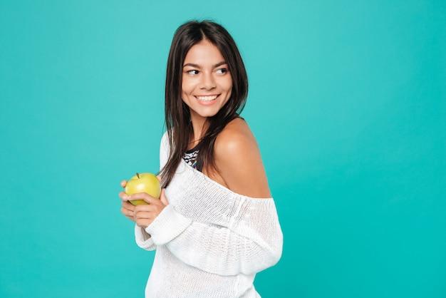 Alegre mulher jovem e atraente em pé e segurando a maçã vermelha