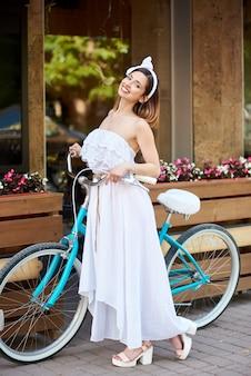 Alegre mulher jovem e atraente sorrindo alegremente segurando sua bicicleta