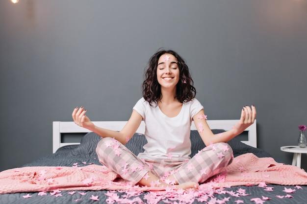 Alegre mulher jovem e bonita de pijama com cabelo castanho encaracolado meditando na cama em enfeites rosa. modelo feliz sorrindo de olhos fechados, expressando verdadeiras emoções, desfrutando do conforto de casa