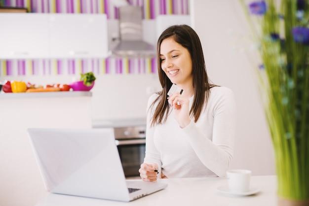 Alegre mulher jovem e bonita está usando seu laptop, mantendo o cartão do banco e tomando café.