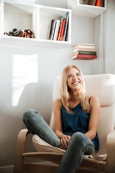 Alegre mulher jovem e bonita sentada na cadeira em casa
