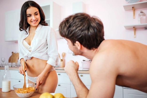 Alegre mulher jovem e sexy ficar na cozinha de biquíni e camisa. ela flocos sem graça com leite. modelo, olhar para o homem e sorrir. cara olha para ela.