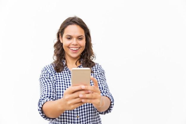Alegre mulher latina com smartphone assistindo conteúdo engraçado