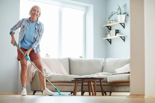 Alegre mulher lavando o chão em casa