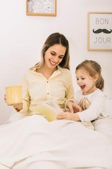 Alegre mulher lendo livro com a filha na cama