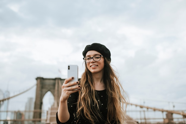Alegre, mulher, levando, um, selfie, com, a, ponte brooklyn, eua