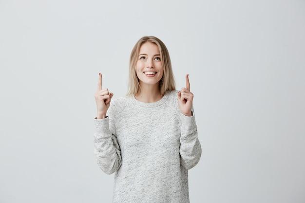 Alegre mulher loira vestindo blusa de manga comprida, olhando para cima, apontando os dedos no espaço da cópia acima da cabeça.