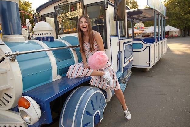 Alegre mulher morena de cabelos compridos com vestido leve de verão, sentada no vagão do trem a vapor no parque de diversões em um dia quente de sol, segurando algodão doce na vara
