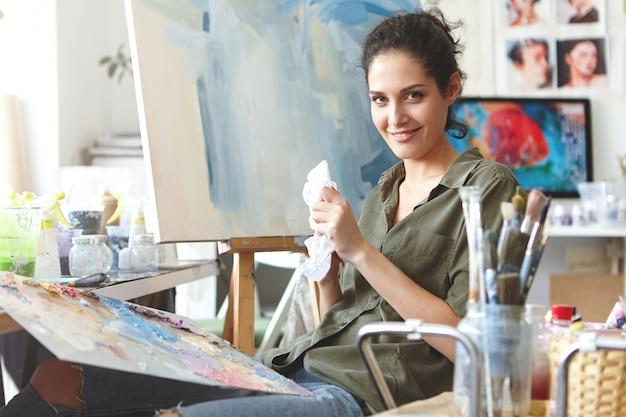 Alegre mulher morena sentada na oficina, desenhando imagens coloridas em cavalete, usando óleos brilhantes. pintor profissional, contente por ter inspiração para a pintura. profissão, conceito de ocupação