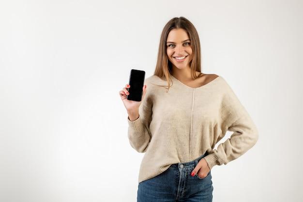 Alegre mulher mostrando a tela em branco vazia telefone na mão isolado sobre o branco