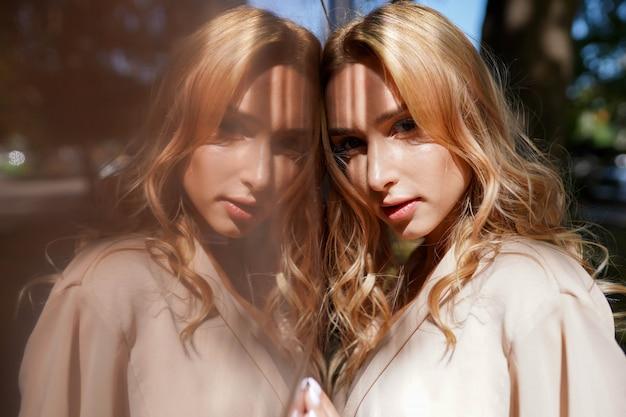 Alegre mulher na rua na luz do sol, menina loira atraente em dia de verão