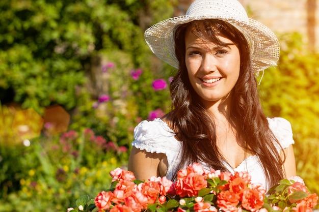 Alegre mulher no jardim de flores de verão