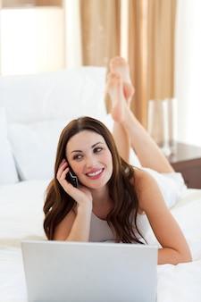 Alegre mulher no telefone usando seu laptop deitado na cama