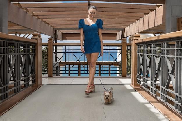 Alegre mulher passeando com o cachorro no terraço do hotel