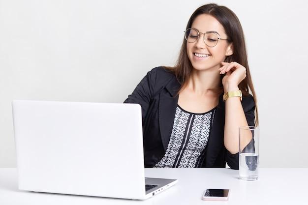 Alegre mulher positiva assiste filme interessante no computador portátil, usa óculos transparentes para uma boa visão, vestida com roupas formais, isoladas sobre parede branca, goza de wifi grátis