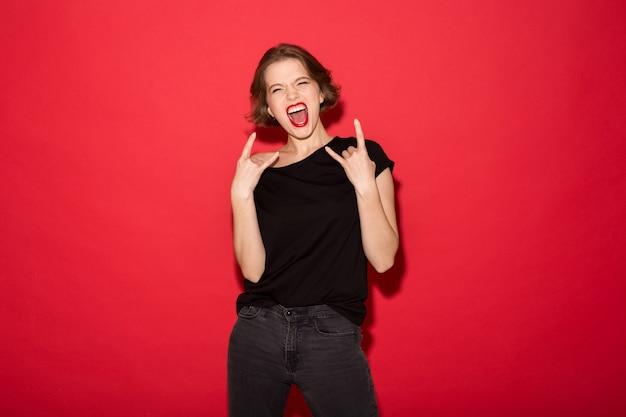 Alegre mulher punk gritando e mostrando gestos de rock enquanto olha