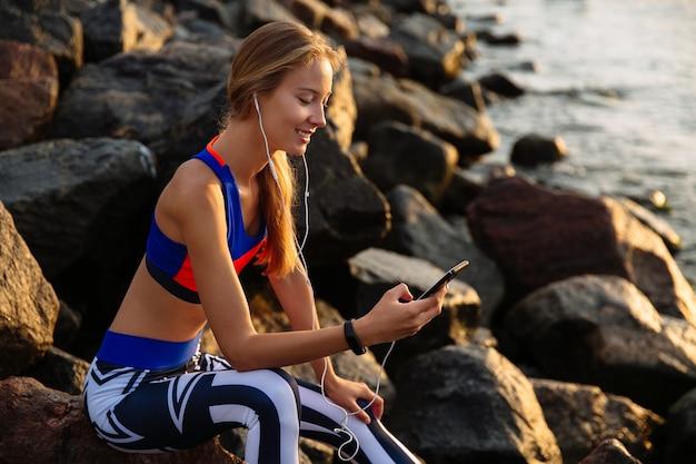 Alegre mulher saudável em fones de ouvido, ouvir música enquanto estiver usando um smartphone