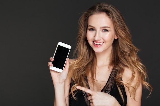 Alegre mulher segurando e apontando no telefone móvel de tela em branco