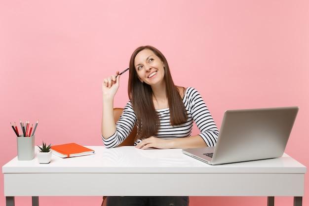 Alegre mulher segurando o lápis perto da cabeça, olhando para cima, acho que sonhando sentar-se trabalhar na mesa branca com laptop pc contemporâneo isolado no fundo rosa pastel. conceito de carreira empresarial de realização. copie o espaço.