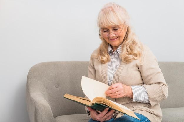 Alegre mulher sênior sentada no sofá lendo o livro