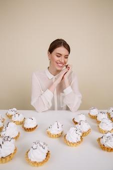 Alegre mulher sentada à mesa com cupcakes e sorrindo