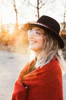 Alegre mulher sorrindo na rua com óculos da moda e estilo moderno.