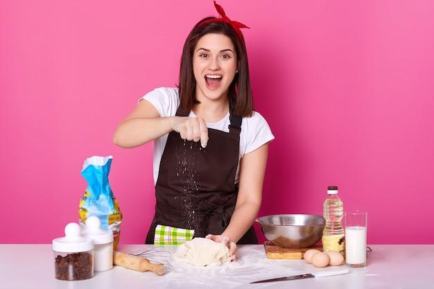 Alegre mulher trabalha na cozinha, quer preparar bolos caseiros, alegremente polvilha farinha na massa, lokks na câmera com a boca aberta. governanta veste camiseta casual, avental marrom e faixa para o cabelo.