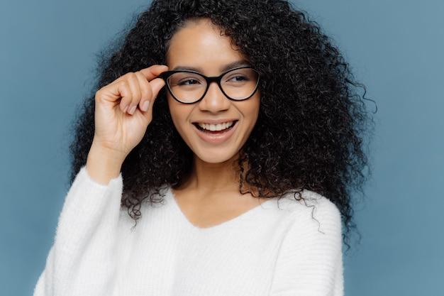 Alegre mulher usa óculos, mantém a mão no quadro, parece alegremente de lado