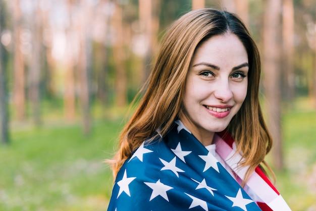 Alegre mulher vestindo a bandeira do eua nos ombros